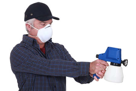 air filter: Man in a mask with a paintsprayer Stock Photo