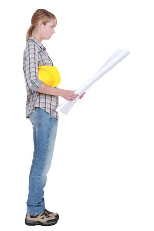 Female construction worker stood reading plans Stock Photo - 12132218
