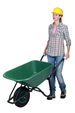 Woman wheeling wheelbarrow photo
