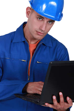 Handsome tradesman using a laptop Stock Photo - 12132615
