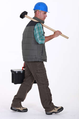 Construction worker carrying tools photo