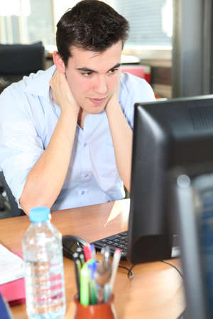 Young man holding his neck in front of a desktop computer photo