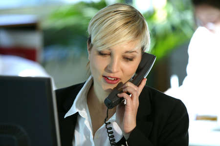 half length posed: Blond office worker using land-line telephone