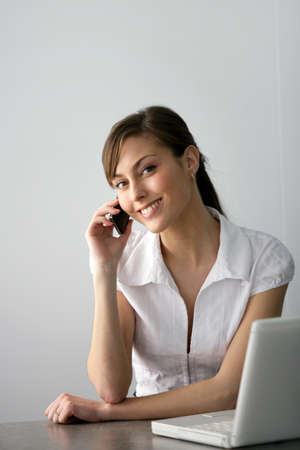 Friendly businesswoman with mobile phone and laptop Stock Photo - 12132338