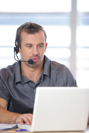 telephone headsets: Man working in an office Stock Photo