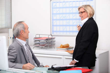 Mature couple working in an office photo