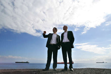 Men in suit chatting at the seaside photo
