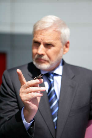 Senior businessman pointing his finger photo