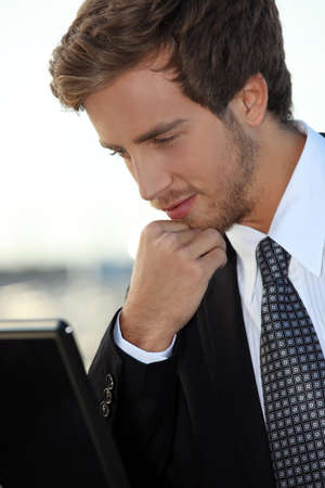 Bearded young exec with a laptop computer photo