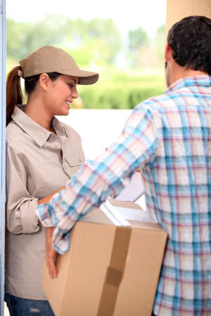 Man signing for a parcel at the front door photo