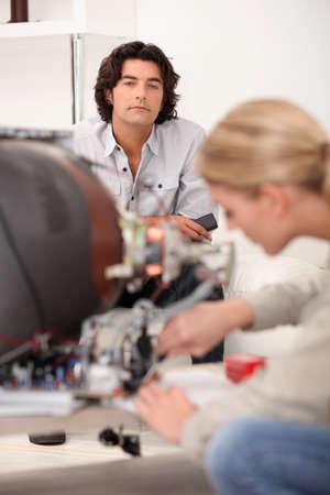 cathode ray tube: Man watching a woman repair a TV set