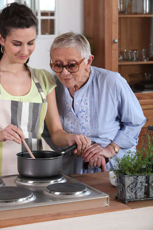 care at home: Young woman cooking for an elderly lady