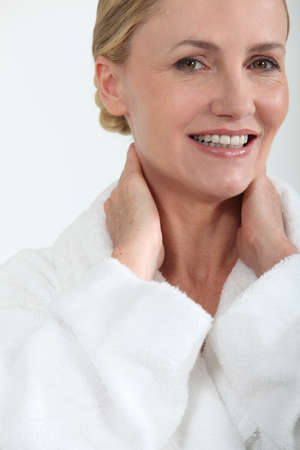 Woman in bath robe smiling with hands behind neck photo