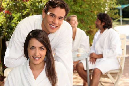 toweling: Young couple in bathrobes sitting on a terrace with friends