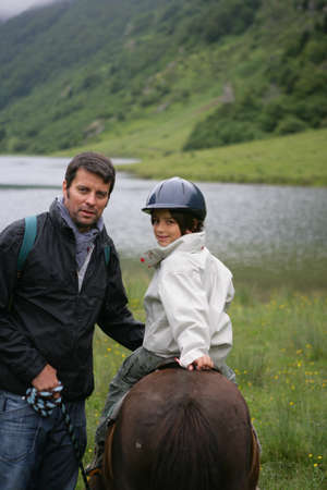 Man teaching his child how to ride a horse photo