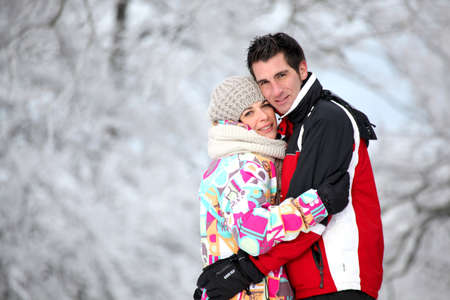 Couple in ski jackets hugging on a winter photo