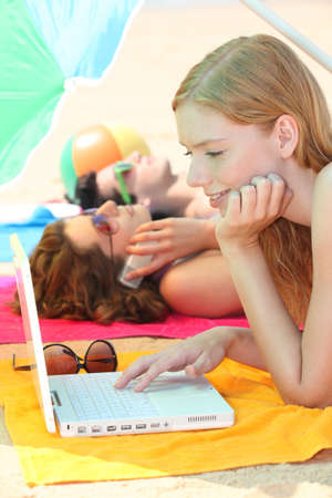 Three female teenagers with a laptop on the beach photo