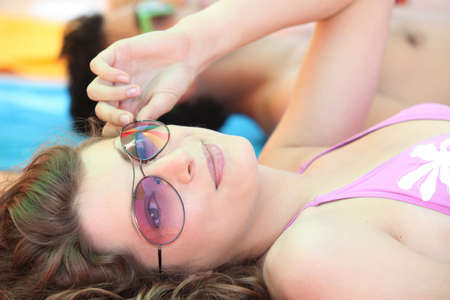 tinted: Young woman wearing sunglasses and sunbathing at the beach Stock Photo