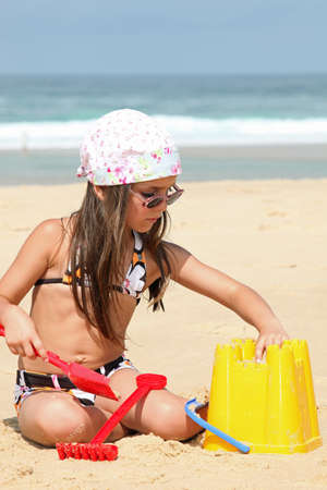 head in the sand: Young girl building  sandcastle