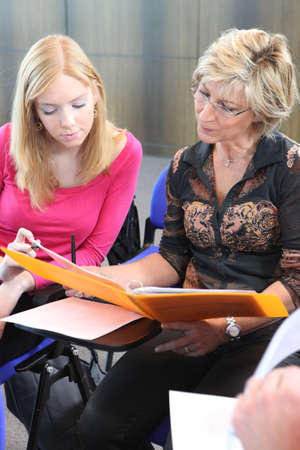 Two women discussing work in a folder photo