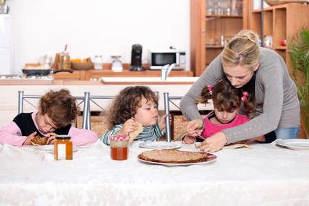 guardería: Los niños pequeños comiendo crepes Foto de archivo