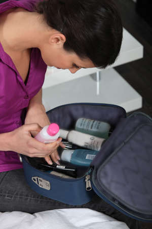 Young woman packing vanity case photo