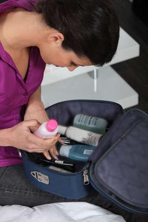 vanity bag: Young woman packing vanity case