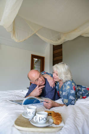 Senior couple having breakfast in bed photo