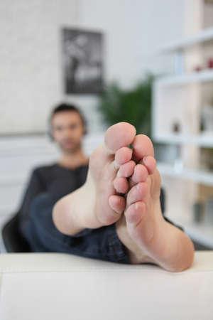 sprawled: Bare-footed man Stock Photo