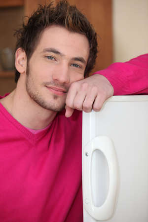 young man posing with arm on fridge door photo