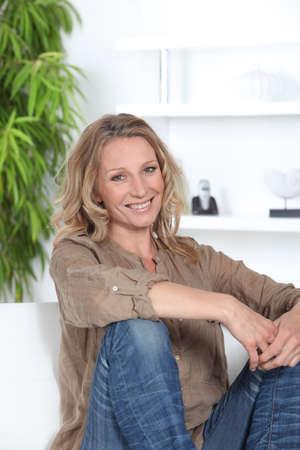 Woman sitting on the sofa Imagens