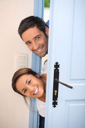 Young couple poking their heads around the front door photo