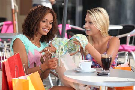 tomando refresco: Amigos que comparan las compras en un caf�
