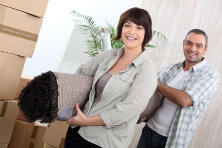 Couple with rolled up carpet surrounded by boxes photo