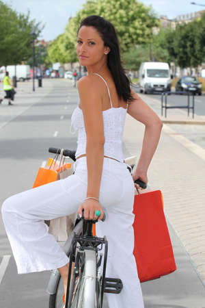 Woman with store bags riding a bike in the city photo