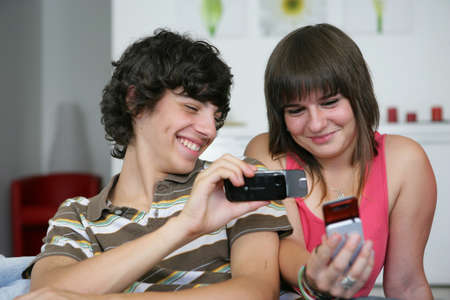 adolescence: Teens looking at pictures on their mobile phones