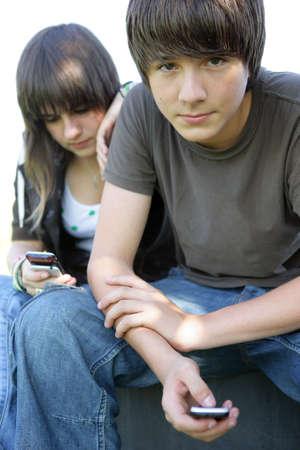 adolescentes chicas: Pareja de adolescentes mensajes de texto en sus celulares