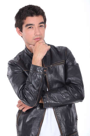 hand on chin: portrait of a young man with leather jacket