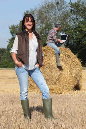 Attractive lady farmer standing in front of her husband on a haystack using a laptop with the screen left blank photo