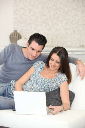 dark haired: couple on couch with computer Stock Photo