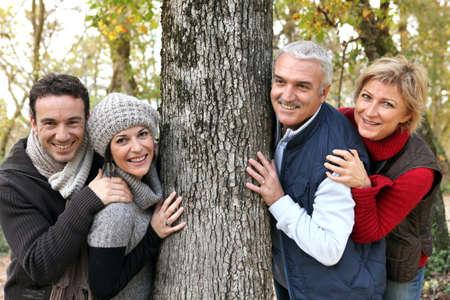 vida social: Adulto de la familia alrededor de un árbol Foto de archivo