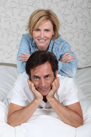 settle back: Married couple relaxing on bed