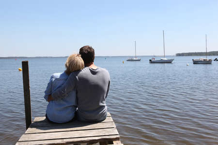 40 45: Couple sitting on the end of a pontoon