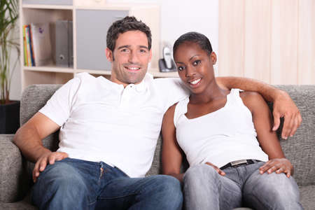 mixed ethnicities: Mixed race couple sat on couch