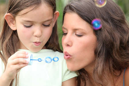 Mother and daughter blowing bubbles photo