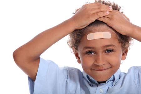 Jongetje met pleister op het hoofd Stockfoto