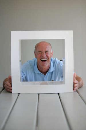 Senior Blick durch ein Bilderrahmen Standard-Bild