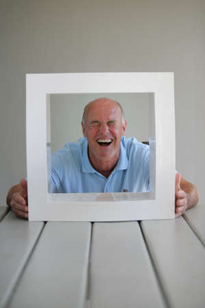 senior looking through a picture frame photo