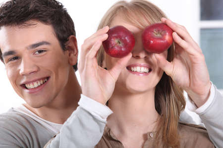 all smiles: young man holding red apples before girfriend