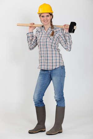 workwoman: Tradeswoman carrying a mallet
